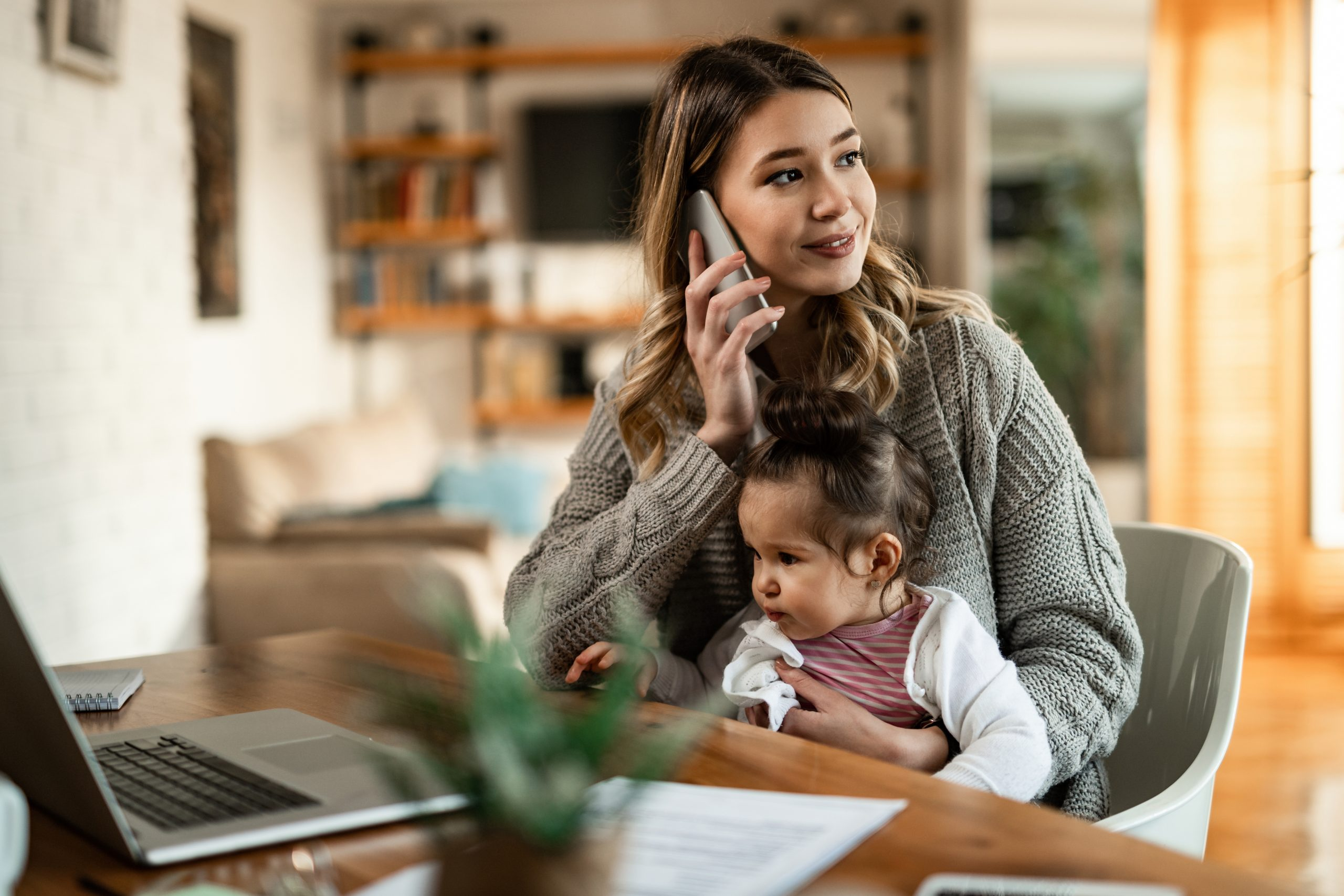 Young mother with small daughter talking on the phone at home.