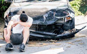Man with wrecked car following a crash