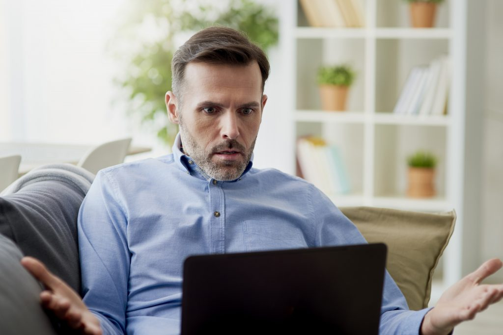 Angry man working home on a computer