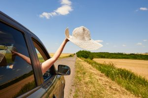 Female hand holding their hat out the car window during a road trip.