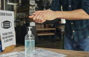 Man rubbing hands together using hand sanitiser in restaurant