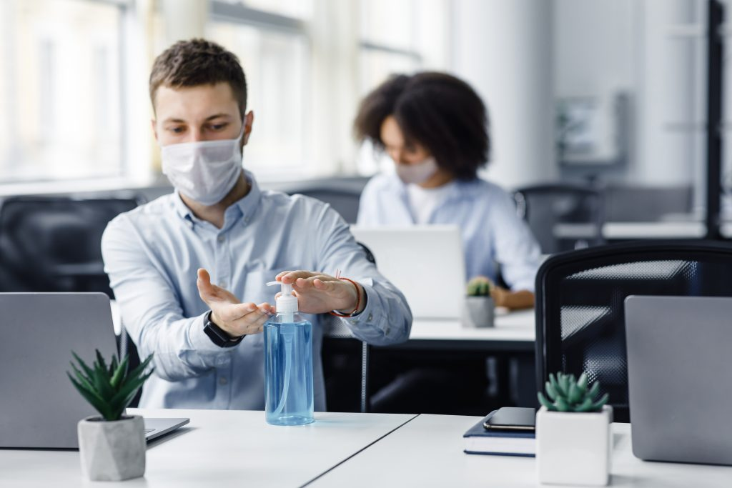 Rules for safety health during coronavirus outbreak. Man in protective mask treat his hands with antiseptic at workplace with laptop